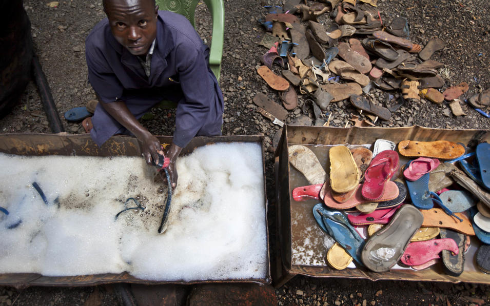 In this photo taken Monday, April 29, 2013, a worker washes and scrubs discarded flip-flops prior to them being sorted and carved into toy animals, at the Ocean Sole flip-flop recycling company in Nairobi, Kenya. The company is cleaning the East African country's beaches of used, washed-up flip-flops and the dirty pieces of rubber that were once cruising the Indian Ocean's currents are now being turned into colorful handmade giraffes, elephants and other toy animals. (AP Photo/Ben Curtis)