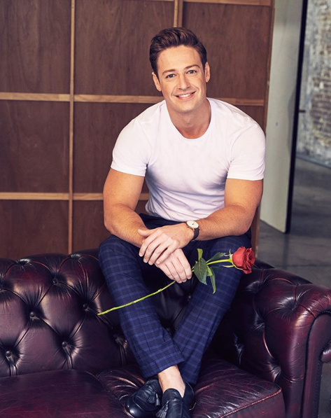 A photo of The Bachelor Australia Matt Agnew wearing a white t-shirt and holding a red rose while sitting on a couch.