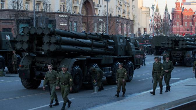 Sejumlah tentara Rusia berjalan di dekata kendaraan militer yang memenuhi jalanan saat melakukan latihan untuk parade militer Hari Kemenangan di Moskow, Rusia (3/5). (AP Photo / Pavel Golovkin)