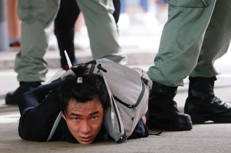 A man lies on the ground as he is detained by riot police during a march against the national security law at the anniversary of Hong Kong's handover to China from Britain in Hong Kong
