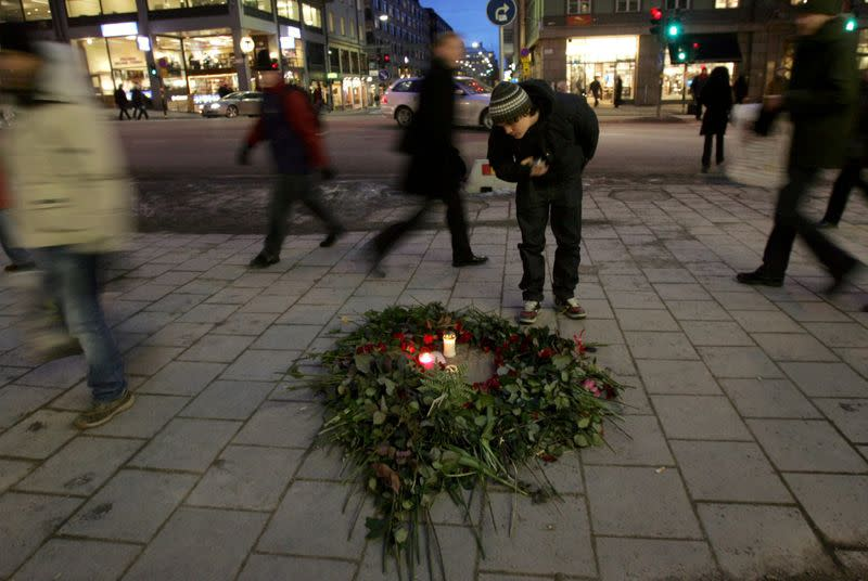 FILE PHOTO: A man bends over a bunch of roses and lit candles on a pavement in Stockholm