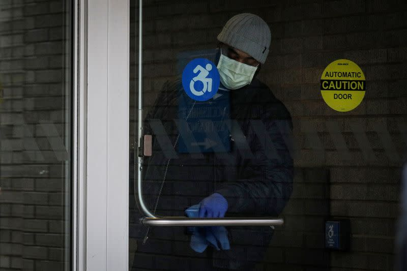 A member of the hospital staff cleans the door at Mount Sinai Hospital, during the outbreak coronavirus disease (COVID-19)  outbreak, in New York