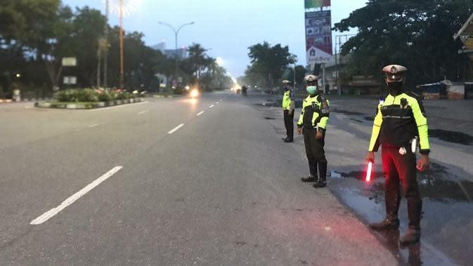 Sejumlah personel Polresta Pekanbaru menjaga Jalan Jenderal Sudirman agar tidak dijadikan arena balap liar. (Liputan6.com/M Syukur)