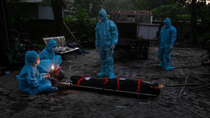 Kerabat dengan mengenakan alat pelindung diri melakukan ritual selama kremasi seseorang yang meninggal karena virus corona COVID-19 di Gauhati, India pada 28 September 2020. (AP Photo/Anupam Nath)