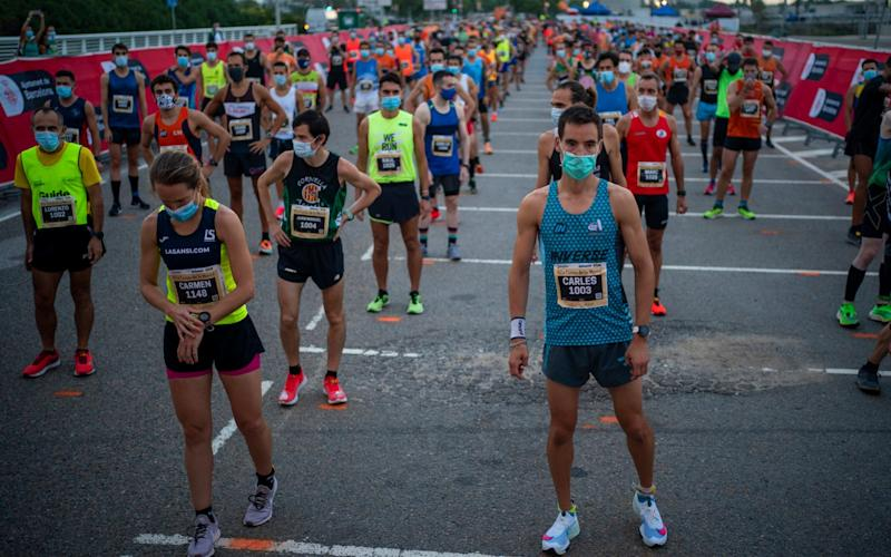 """Athletes wearing face masks keep their positions before taking part in """"La Cursa de la Mercè"""" race, one of the most emblematic events of Barcelona's sporting calendar - AP"""