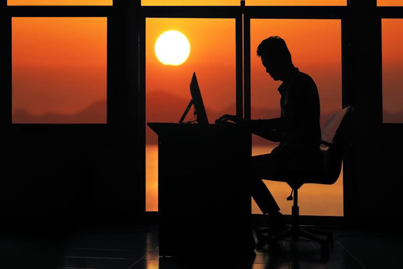 silhouette of man in office working at desk as sun rises, married for money