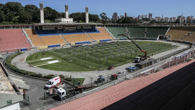 Lokasi pembangunan rumah sakit lapangan sementara untuk menampung pasien terinfeksi Covid-19 di stadion Pacaembu, di Sao Paulo, Senin (23/3/2020). Sejumlah klub sepakbola papan atas Brasil meminjamkan stadion untuk diubah menjadi rumah sakit atau klinik darurat virus corona. (NELSON ALMEIDA/AFP)