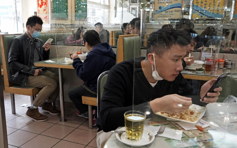 Customers have lunch with a transparent plastic panel setup on the table to isolate each others to prevent virus spreading in Hong Kong, Feb. 12, 2020. (AP Photo/Kin Cheung)