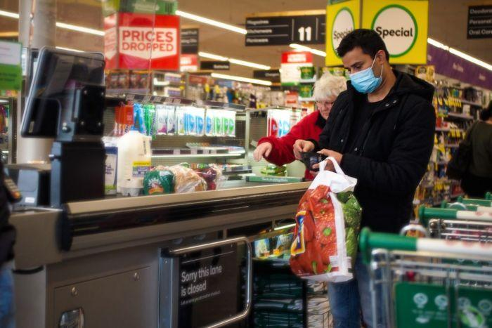 A man in a blue surgical mask opens his wallet at the checkout in Woolworths, while a woman behind him is not wearing a mask.