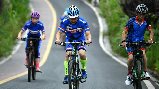 Sejumlah orang bersepeda di sepanjang jalur sepeda di Desa Sanliya di Wilayah Pingli, Provinsi Shaanxi, China barat laut (23/7/2020). Jalur sepanjang 40 kilometer yang membentang di alam bebas ini menawarkan pengalaman yang menyenangkan bagi pesepeda. (Xinhua/Zhang Bowen)
