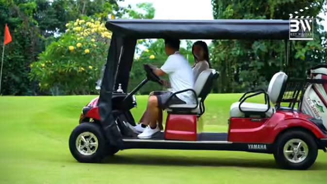 Boy dan Ovi keliling halaman belakang menggunakan mobil yang biasa digunakan untuk main golf. (Youtube/Boy William)