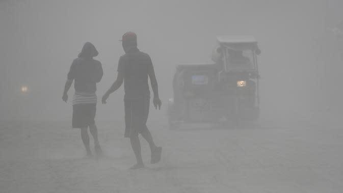 Penduduk berjalan saat gunung berapi Taal memuntahkan abu vulkanik di Lemery, provinsi Batangas, Filipina, Senin (13/11/2020). Erupsi gunung Taal memaksa puluhan ribu orang mengungsi serta membuat sekolah-sekolah dan toko di Manila tutup. (AP/Aaron Favila)