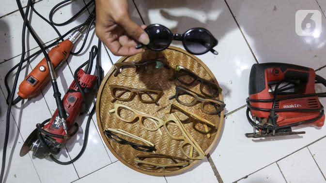 Berbagai model kacamata dari limbah kayu dan peralatan yang digunakan di Jalan Salak, Pamulang, Tangerang Selatan, Senin (12/10/2020). Produksi kacamata yang terbuat dari limbah kayu jati landa dan kayu sonokeling dijual dengan harga Rp 300 ribu hingga diatas Rp 1 juta. (Liputan6.com/Fery Pradolo)