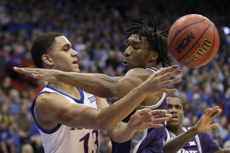 Kansas guard Tristan Enaruna (13) passes around Kansas State forward Xavier Sneed, right, during the second half of an NCAA college basketball game in Lawrence, Kan., Tuesday, Jan. 21, 2020. Kansas defeated Kansas State 81-59. (AP Photo/Orlin Wagner)