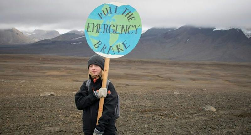 "A female youth shown in Iceland holding a sign saying ""pull the emergency brake""."