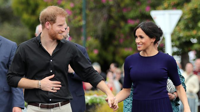Pangeran Harry dan Meghan Markle berjalan di Taman Pemerintah Rotorua, Selandia Baru, Rabu (31/10). Pangeran Harry dan Meghan Markle sedang dalam tur tiga minggu di Australia, Selandia Baru, Tonga, dan Fiji. (Michael Bradley/Pool/AFP)