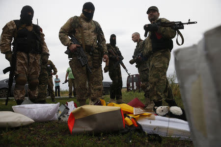 Pro-Russian separatists look at passengers' belongings at the crash site of Malaysia Airlines flight MH17, near the settlement of Grabovo in the Donetsk region, July 18, 2014. REUTERS/Maxim Zmeyev