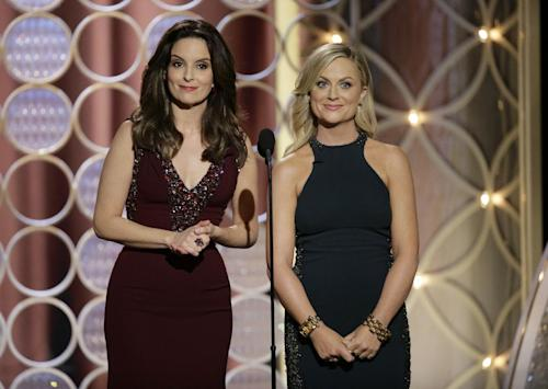 This image released by NBC shows hosts Tina Fey, left, and Amy Poehler during the 71st annual Golden Globe Awards at the Beverly Hilton Hotel on Sunday, Jan. 12, 2014, in Beverly Hills, Calif. (AP Photo/NBC, Paul Drinkwater)