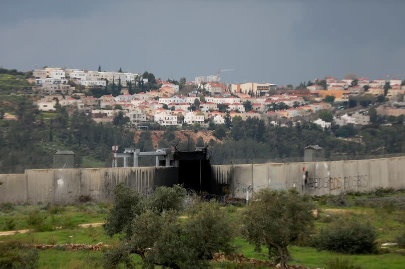 FILE PHOTO: A view shows the Jewish settlement of Modiin Illit in the background and the Israeli barrier in the foreground, in the village of Bilin in the Israeli-occupied West Bank