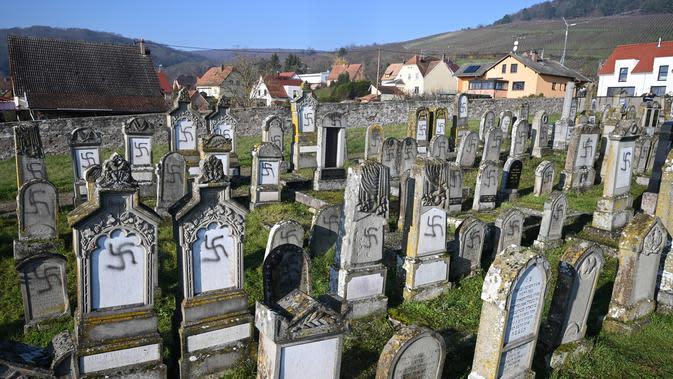 Suasana makam yang dicoreti lambang swastika Nazi di pemakaman Yahudi, Westhoffen, dekat Strasbourg, Prancis, Rabu (4/12). Sedikitnya 107 makam menjadi sasaran vandalisme dengan dicoreti lambang swastika Nazi. (AFP/Patrick Hertzog)