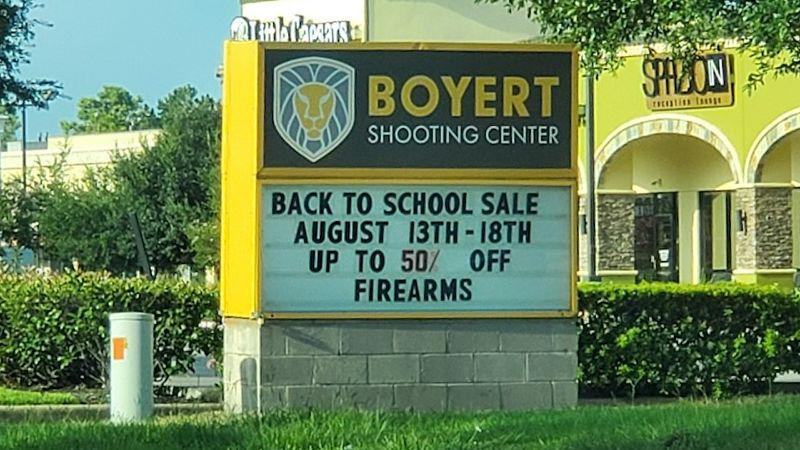 "Sign outside Boyert Shooting Centre in Texas saying: ""back to school sale: August 13th - 18th up to 50 percent off firearms""."