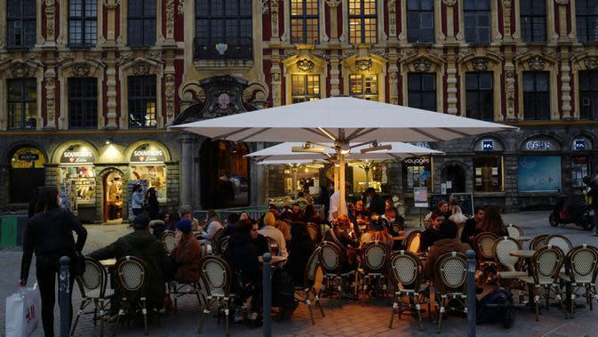 Orang-orang menikmati makanan di Lille, Prancis, Jumat (16/10/2020). Prancis mengerahkan 12.000 polisi untuk memberlakukan jam malam baru mulai Jumat malam hingga bulan depan untuk memperlambat penyebaran COVID-19. (AP Photo/Michel Spingler)