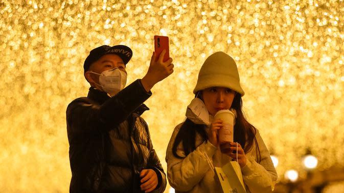 Orang-orang berhenti sejenak di sebuah jalan kawasan perniagaan di Wuhan, Provinsi Hubei, China tengah, pada 30 Maret 2020. Jalan-jalan kawasan perniagaan di Wuhan kembali ramai seiring meredanya wabah COVID-19. (Xinhua/Shen Bohan)