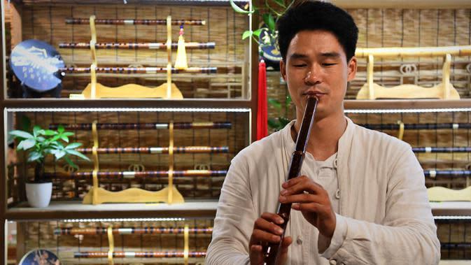 Seorang penjaga toko menampilkan pertunjukan bagi para wisatawan di sebuah toko di kota kuno Luoyi di Luoyang, Provinsi Henan, China tengah, pada 7 Juli 2020. Berbagai bentuk tur malam hari di Luoyang menarik banyak wisatawan dan mendongkrak perekonomian. (Xinhua/Li An)