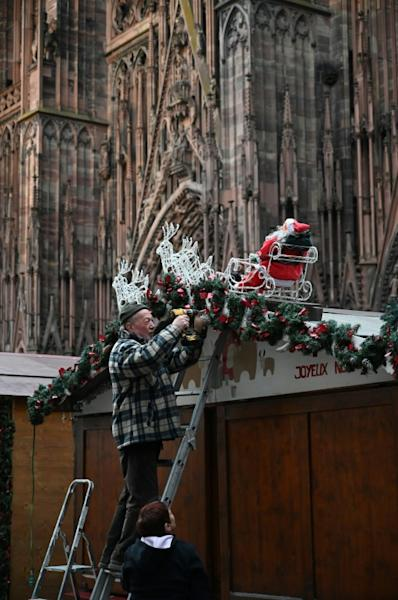 A worker installs decorations at the market, which will see a beefed up security presence this year