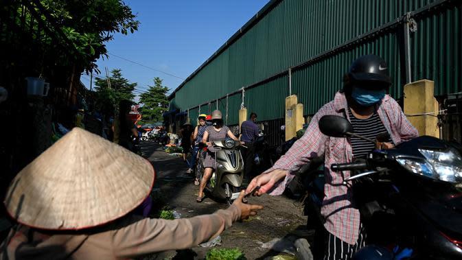 Seorang wanita membeli sayuran di pasar grosir di Hanoi (26/8/2020). (AFP Photo/Manan Vatsyayana)