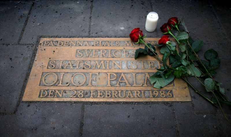 FILE PHOTO: Roses are laid on a plaque marking the location where Swedish Prime Minister Olof Palme was killed 25 years ago in Stockholm