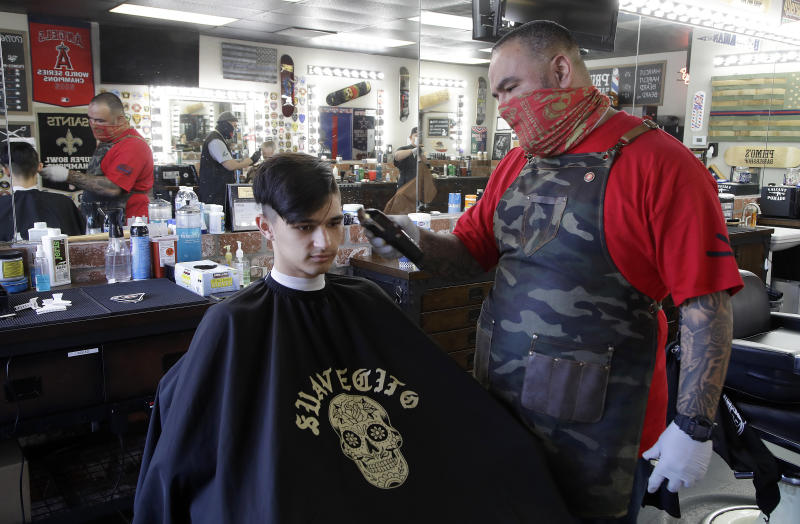 Juan Desmarais, right, owner of Primo's Barbershop, cuts the hair of Ian Hothi on Monday, May 4, 2020, in Vacaville, Calif. Desmarais, a former US Marine, re-opened his business on Friday, May 1, 2020, after realizing it could be months before he had permission to operate due to COVID-19 restrictions. (AP Photo/Ben Margot)