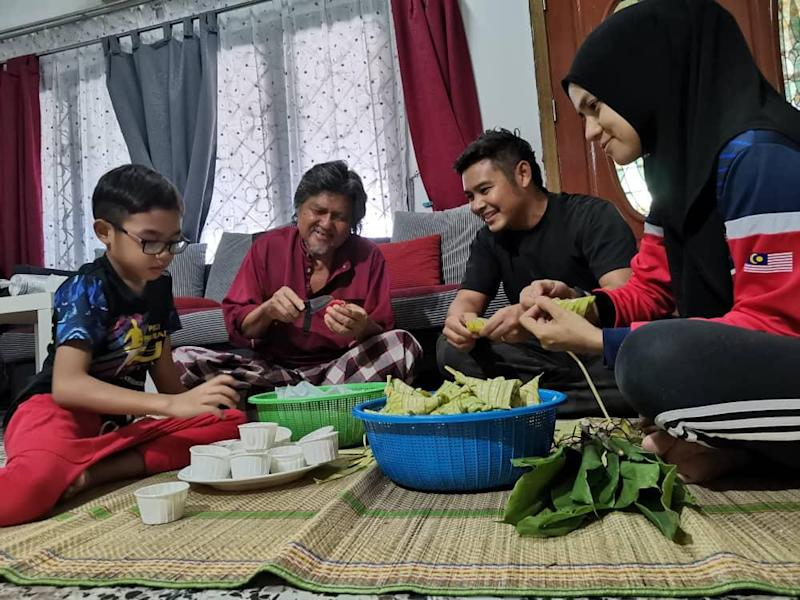 Ahmad Hazeeq Ahmad Hisham (second from right) helping to get ready some Raya food with his son Aryan (left), father-in-law Mohd Yussof Abdullah and wife Nur Farhana Mohd Yussof.