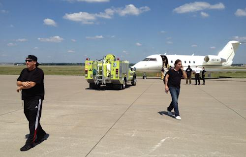 In this photo provided by Chuck Brennan, Dave Ungar, the tour manager for the rock band Dokken, left, and Craig Bradford, tour manager for Ratt, walk away from a charter jet that had to make an emergency landing, Saturday, Aug. 17, 2013, in Moline, Ill. The plane, which took off from Moline, returned to the airport early Saturday afternoon after smoke appeared in the cabin at 7,000 feet. No injuries were reported, and the bands took ground transportation to their concert in a suburb of Chicago. (AP Photo/Courtesy Chuck Brennan)