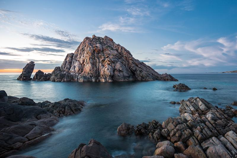 A photo of the triangle-shaped Sugarloaf Rock rising dramatically up out of the ocean in the Margaret River and Dunsborough area of Western Australia.