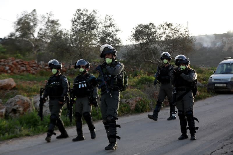 Israeli border police members wear masks as they walk during a Palestinian protest against Israeli settlements, near the town of Beita in the Israeli-occupied West Bank