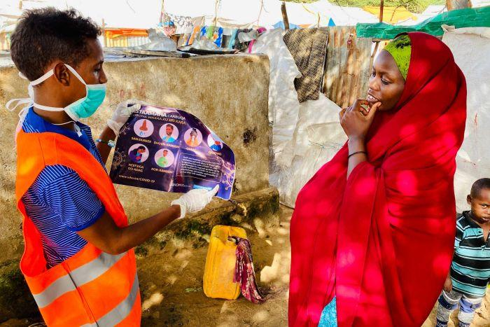 A man wearing a mask shows a woman a pamphlet with health-related instructions.