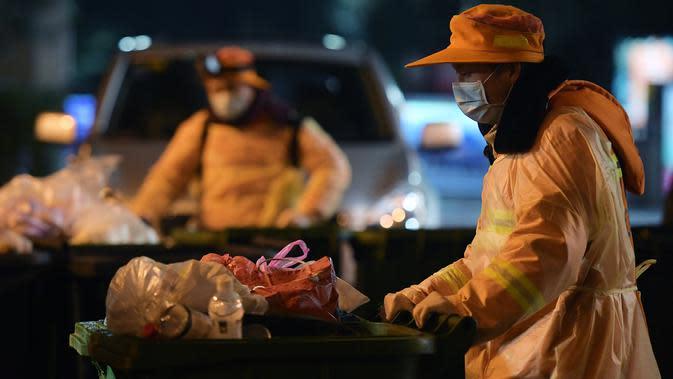 Pekerja sanitasi yang berjaga di pos mereka membersihkan sampah di sebuah daerah permukiman pada malam hari di Wuhan, Provinsi Hubei, China tengah, pada 1 Februari 2020. (Xinhua/Li He)