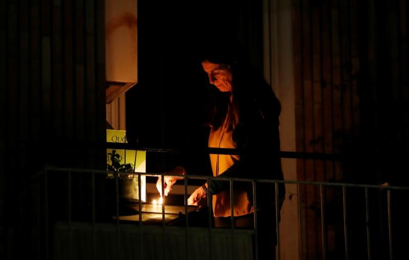 A woman lights a candle on her balcony as faithful across Italy say a prayer for people suffering from coronavirus disease (COVID-19)
