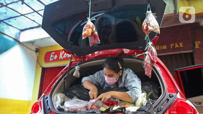 Cynthia (28) mahasiswi perguruan tinggi swasta merapikan dagangannya di Jalan Santosa, Depok, Jawa Barat, Kamis (21/5/2020). Cynthia berjualan berbagai macam sayuran guna memenuhi kebutuhan sehari-hari di tengah pandemi Covid-19. (Liputan6.com/Herman Zakharia)