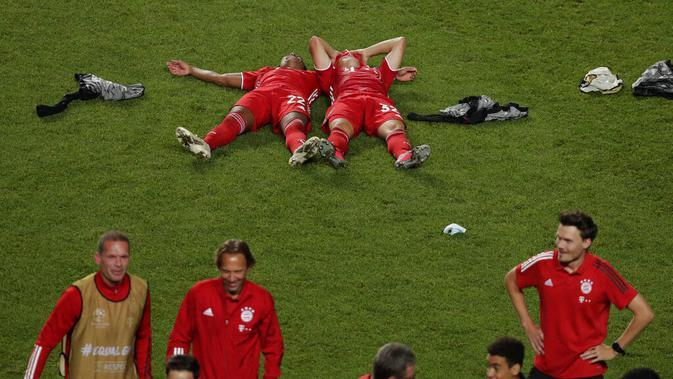 Pemain Bayern Munchen, Serge Gnabry dan Joshua Kimmich tidur di lapangan saat melakukan selebrasi usai menjuarai Liga Champions di Stadion The Luz, Portugal, Senin (24/8/2020). Bayern Munchen berhasil menjadi juara usai menaklukkan PSG 1-0. (Miguel A. Lopes/Pool via AP)