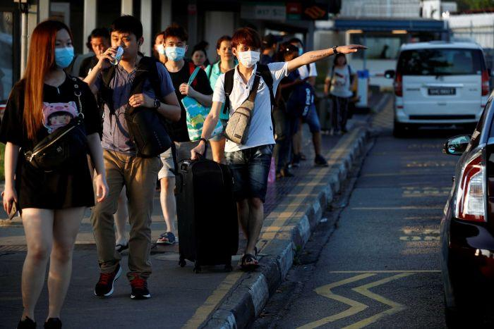 People waring masks line up for cabs in Malaysia.