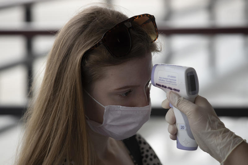 A health officer checks the temperature of a tourist who wants to extend visa at Immigration Bureau in Bangkok, Thailand, Friday, March 27, 2020. Tourists across Asia are finding their dream vacations have turned into travel nightmares as airlines cancel flights and countries close their borders in the fight against the coronavirus pandemic. (AP Photo/Sakchai Lalit)