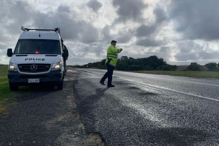 A police officer in hi-vis vest walks across a road with a parked police van behind him