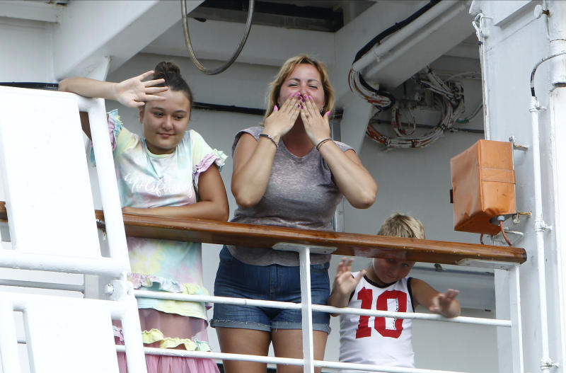 Passengers react from the MS Westerdam docked at the port of Sihanoukville, Cambodia, Saturday, Feb. 15, 2020. After being stranded at sea for two weeks because five ports refused to allow their cruise ship to dock, the passengers of the MS Westerdam were anything but sure their ordeal was finally over. (AP Photo/Heng Sinith)