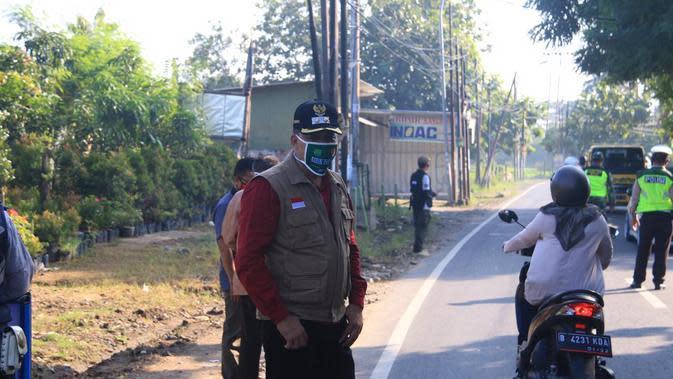 Petugas berjaga di titik check point PSBB di Kota Bekasi. (Liputan6.com/ Bam Sinulingga)