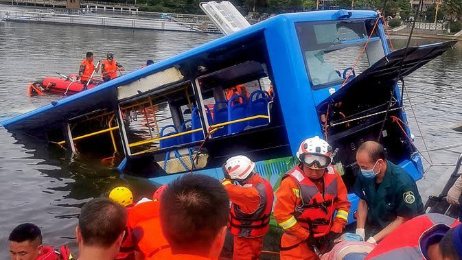 Tim penyelamat berusaha mengevakuasi sebuah bus yang jatuh ke danau di Anshun, provinsi Guizhou, China, Selasa (7/7/2020). Sedikitnya 21 orang tewas usai bus yang membawa siswa untuk mengikuti ujian masuk perguruan tinggi atau gaokao itu menabrak pagar pembatas lalu tercebur ke danau. (STR/AFP)
