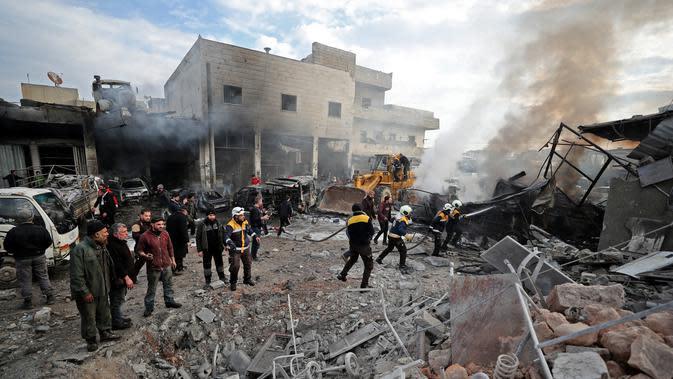 Anggota Syrian Civil Defence atau White Helmets memadamkan api di lokasi serangan udara rezim di Idlib, Suriah, Rabu (15/1/2020). Serangan udara yang dilancarkan pasukan pemerintah menghantam pasar sayur-mayur dan toko-toko reparasi di Idlib. (Omar HAJ KADOUR/AFP)
