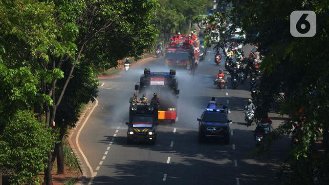 Petugas gabungan melakukan penyemprotan cairan disinfektan di sepanjang jalan raya di wilayah Jakarta Timur, Selasa (25/8/2020). Penyemprotan ini di bagi dua jalur utara dan Selatan. (merdeka.com/Imam Buhori)
