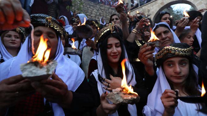 Kelompok Yazidi Irak membawa obor parafin di luar kuil Lalish saat perayaan Tahun Baru Yazidi di lembah dekat Dohuk, Irak (17/4). Agama Yazidi sekilas seperti perpaduan antara Islam, Kristen dan Zoroaster. (AFP/Safin Hamed)